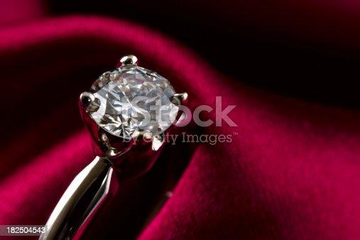 Macro shot of an engagement solitaire diamond ring. Burgundy silk background.