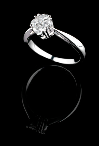 Close up of a Solitaire gold diamond ring on a black background
