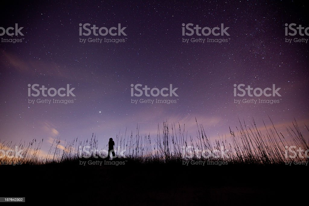 Solitary figure admiring the sky on a clear starry night stock photo