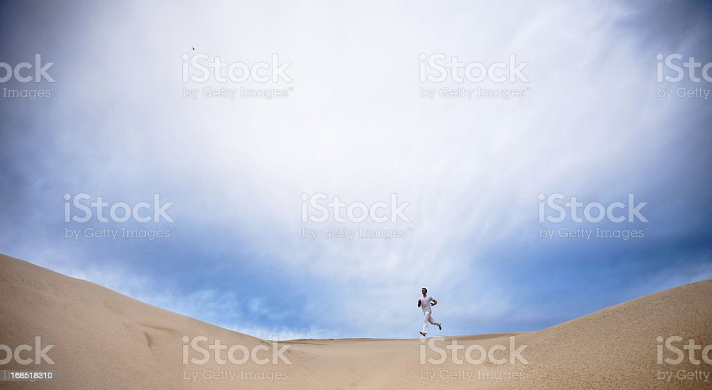 Solitary figure in white running over a hill royalty-free stock photo