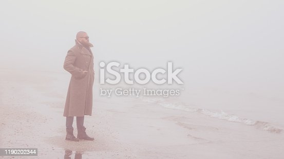 Solitary man with beard and greatcoat is standing by the sea (on the beach) with calm sea and fog and looking away