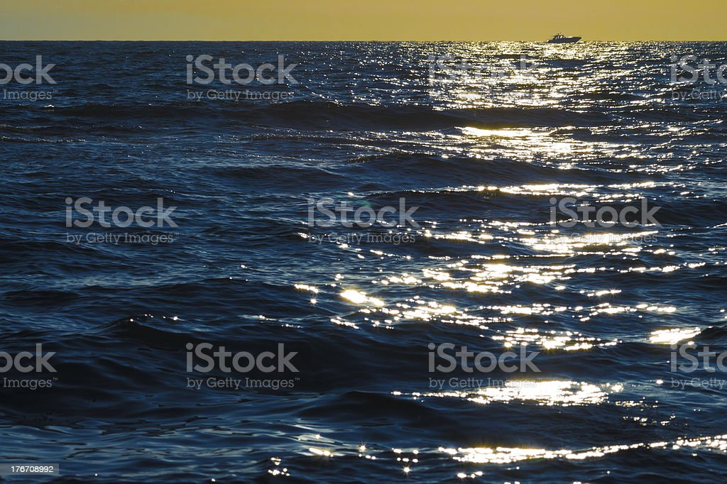 Solitary motorboat cruising the sea at sunset