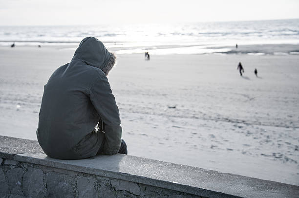 Solitary person in hooded parka coat sits on sea wall alone A person wearing a parka coat sits on a wall looking out at the sea suicide stock pictures, royalty-free photos & images