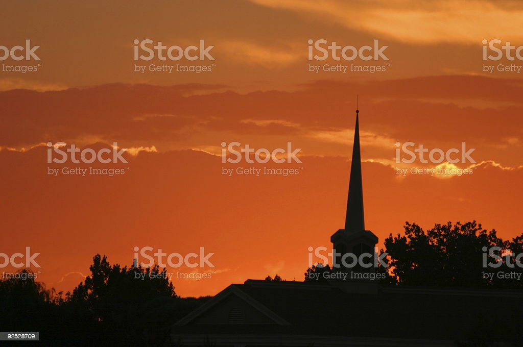 Solitary Silhouetted Steeple Spire Pierces Sunset stock photo