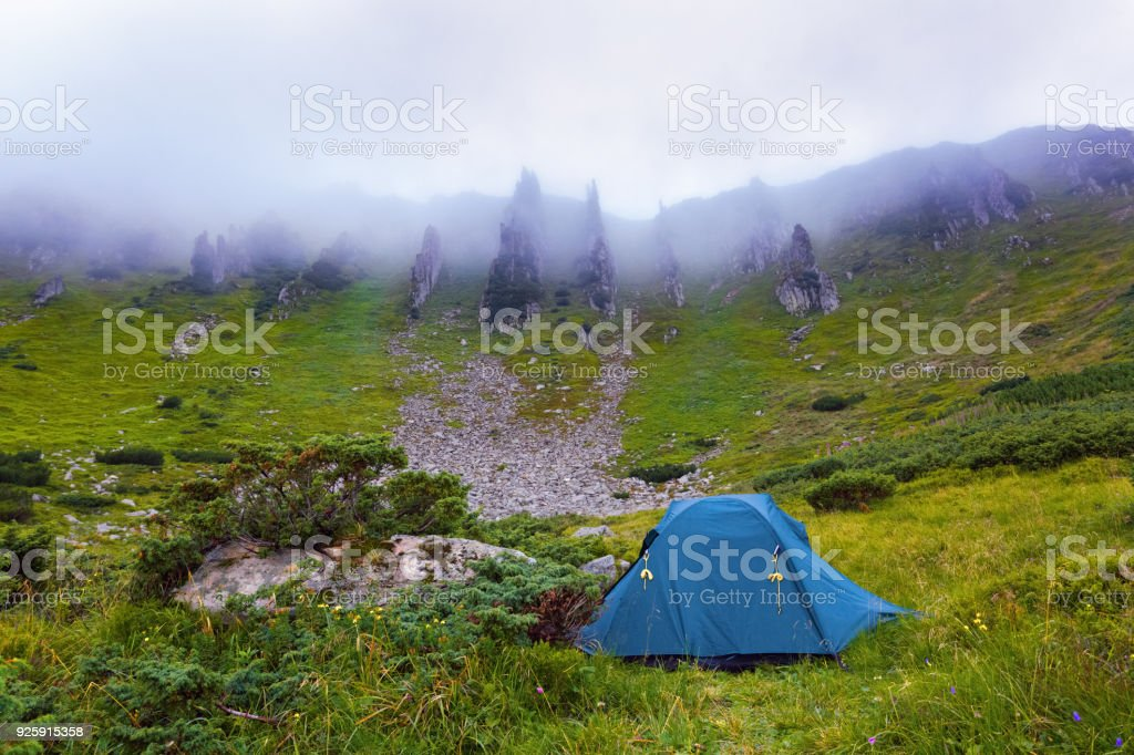A solitary tourist tent stands on a meadow and around headlong rocky mountains and dense fog on a summer morning. stock photo