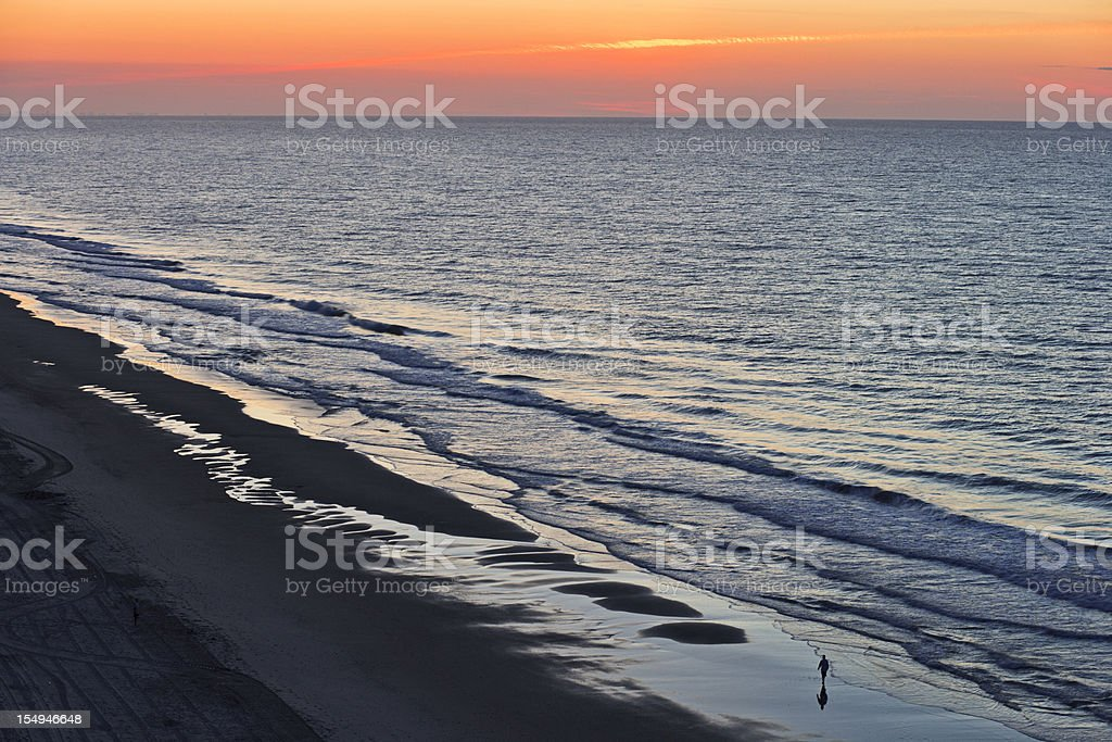 Solitary walker with ocean sunrise or sunset royalty-free stock photo