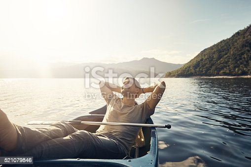 Shot of a young man relaxing in a boat out on a lake