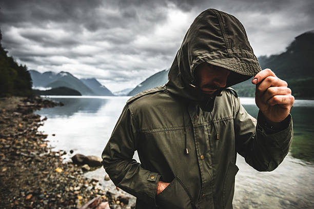 solitude man pensive on the lake side - jacket stock photos and pictures