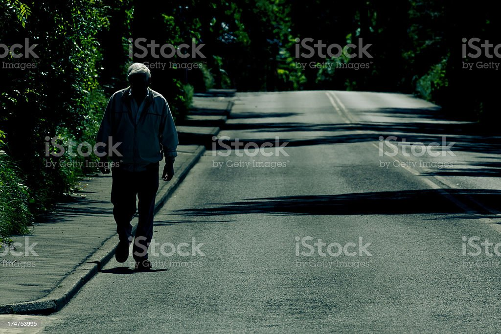 Solitude Old Man Walking Alone On An Empty Road royalty-free stock photo