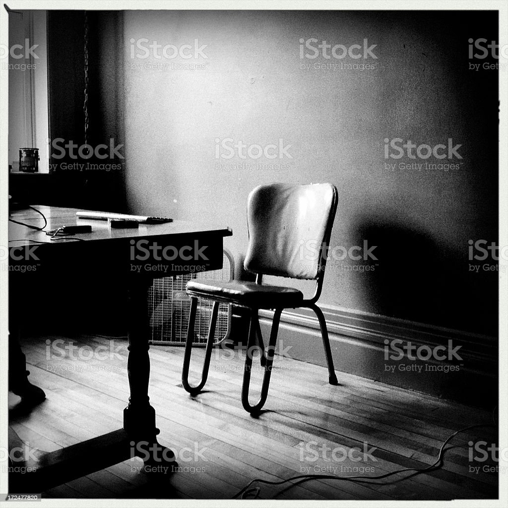 Empty chair in a dark room, solitude concept.