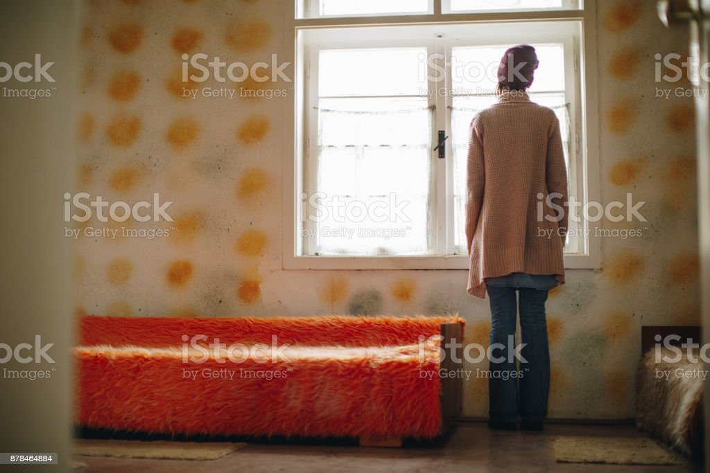 Woman looking through the window,alone at home