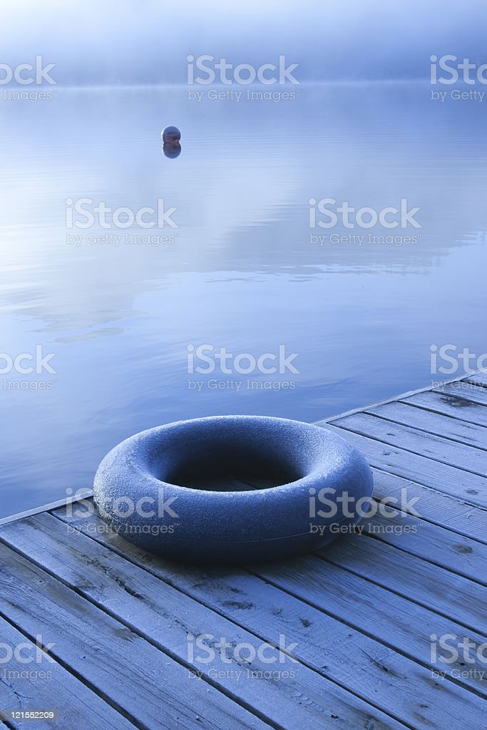 Solitude, tranquility : inner tube on dock in winter stock photo