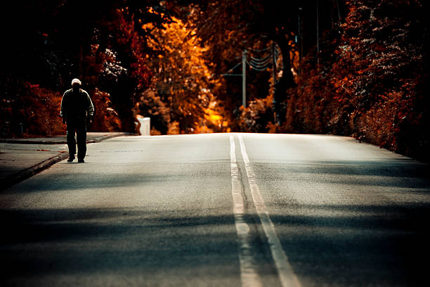 Solitude Walking Alone On An Empty Road stock photo