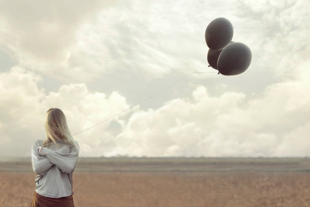 solitude woman with blacks balloons hid her face stock photo