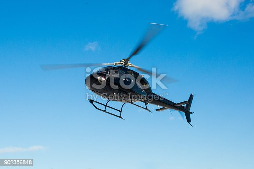 solo black helicopter in blue skies flying