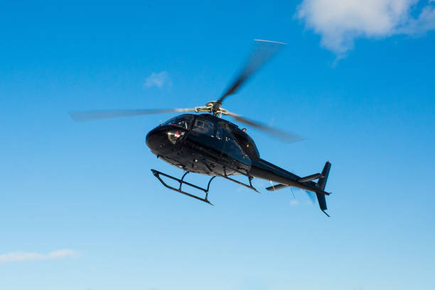 solo black helicopter in blue skies stock photo