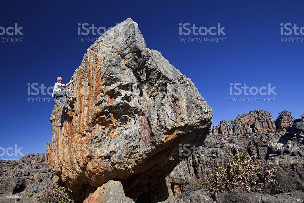 Solo climber A rock climber climbing on a high boulder in Rocklands, Cederberg Mountains, South Africa Boulder - Rock Stock Photo