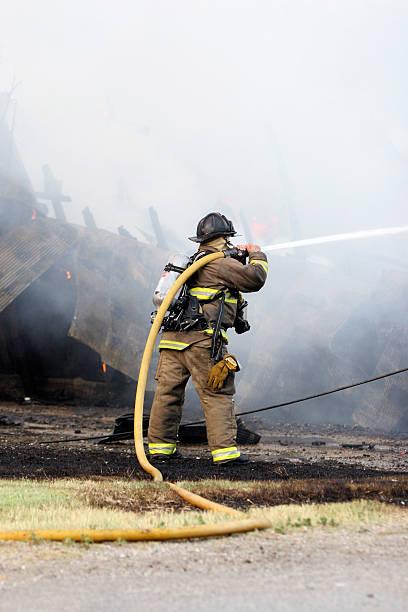Solo Feuerwehrmann putting Wasser auf Scheune fire – Foto