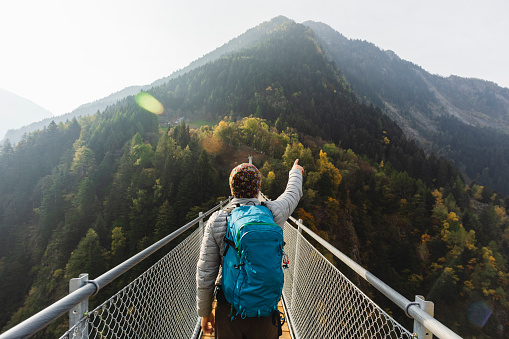 Solo hiker pointing with hand on suspension bridge