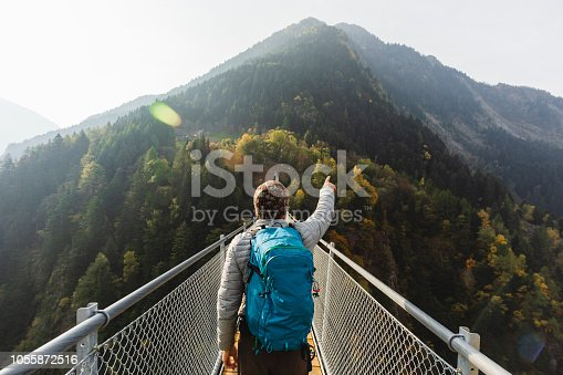 Solo hiker on suspension bridge between two mountain valleys