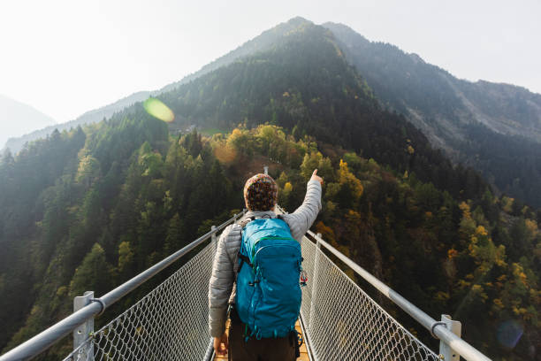 Solo hiker pointing with hand on suspension bridge Solo hiker on suspension bridge between two mountain valleys explorer stock pictures, royalty-free photos & images