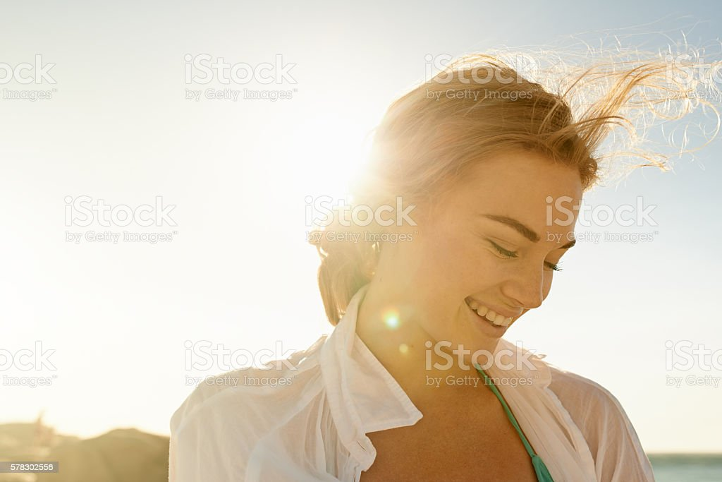 Solo in the sun Shot of a beautiful young woman at the beach Adult Stock Photo