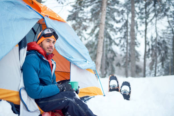 Solo indian man traveller camping through an evergreen winter forest in Canada stock photo