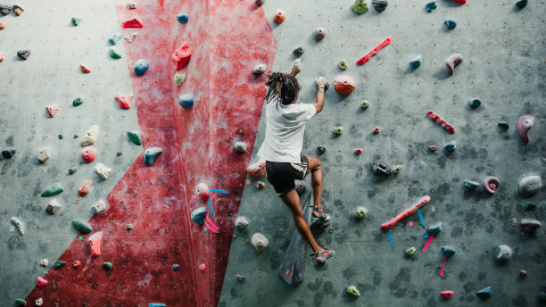 Solo Session At The Climbing Centre One young man is enjoying rock climbing in a climbing centre. passion stock pictures, royalty-free photos & images