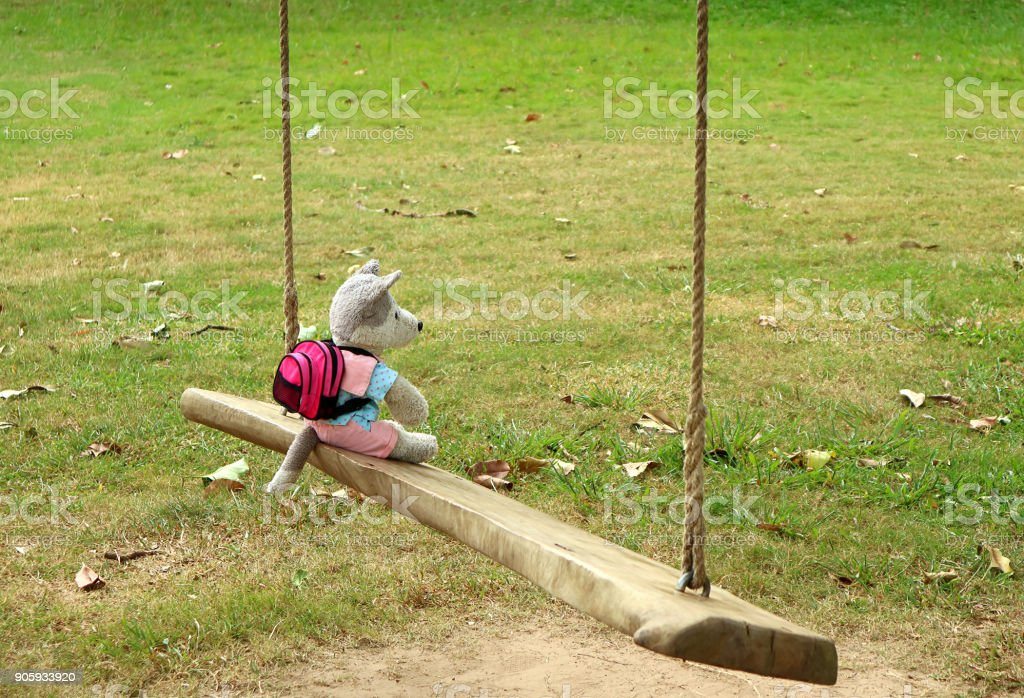 Solo traveler! a cute puppy soft toy with backpack relaxing on a wooden swing in the park stock photo