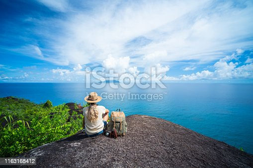 rear view woman with backpack, old manual photo camera and straw hat  sitting relaxing on granite rock watching the calm indian ocean on sunny vacation day