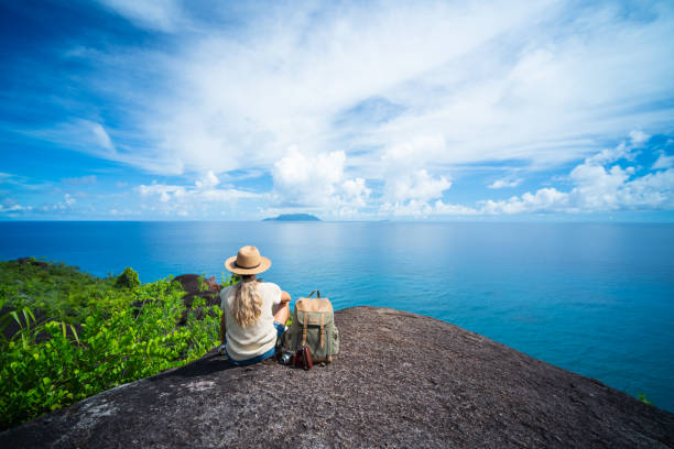 solo traveler back view one woman sitting on rock of tropical island enjoying seaview stock photo
