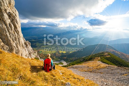 rear view hiking woman with backpack sitting alone on steep slope on sunny autumn day in mountains enjoying view with dramatic sky mountain range down to valley