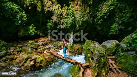 Woman traveling solo crosses wooden bridge at Puente de Dios in San Luis Potosí, Mexico.