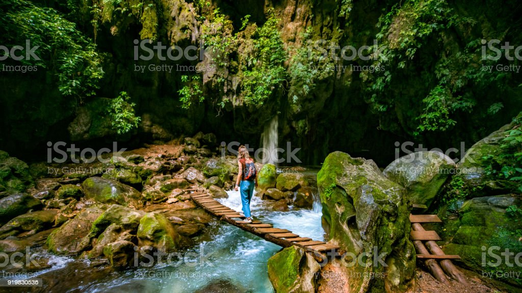 Solo Traveler crossing wooden bridge at Puente de Dios in San Luis Potosí Mexico stock photo