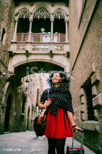 Young woman with suitcase enjoying Barcelona during a business travel