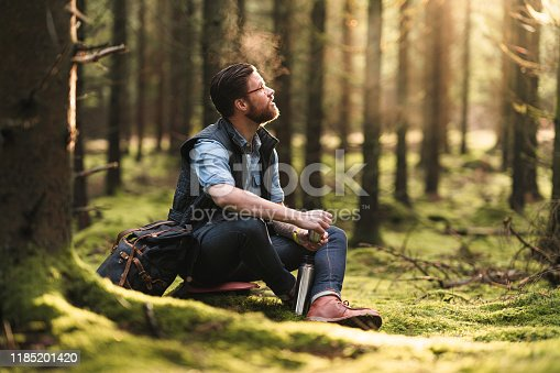A man hiking through pine tree forests in Sweden. He is sitting down to drink some hot coffee.