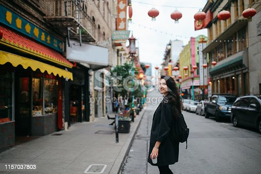 Young woman walking down the Chinatown district in San Francisco, California. She is wearing casual clothing, carrying a cup of coffee to go, enjoying the vibrant and famous Chinese district.