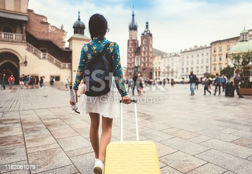 Rear view of woman with suitcase and umbrella relocate to live in Krakow