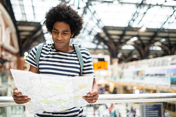solo traveler in london liverpool street station reading the map stock photo