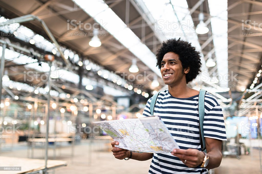 solo traveler in londonspitafields market reading a map stock photo