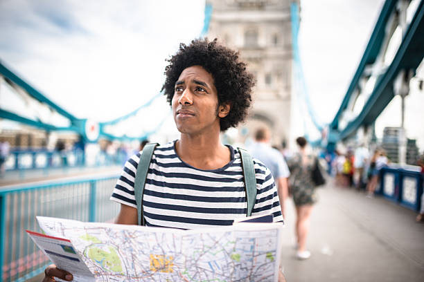 solo traveler in tower bridge area reading a map - 迷う ストックフォトと画像