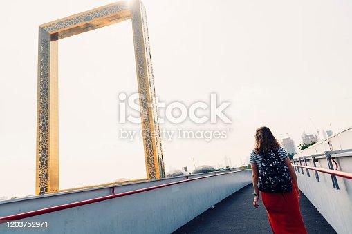 Dubai frame and woman traveler.