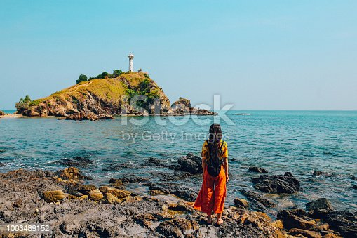 Vintage toned image of a solo traveler young woman, enjoying the beautiful summertime on the island of Koh Lanta, in Krabi province of Thailand. She is wearing colorful summertime clothes, looking at the lighthouse at the very southern end of the island.