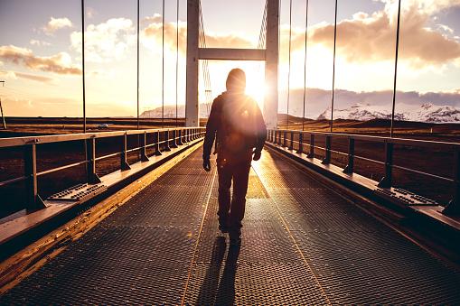 Solo traveler walking on a bridge with arm raised
