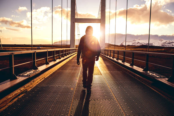 Solo traveler walking on a bridge with arm raised stock photo