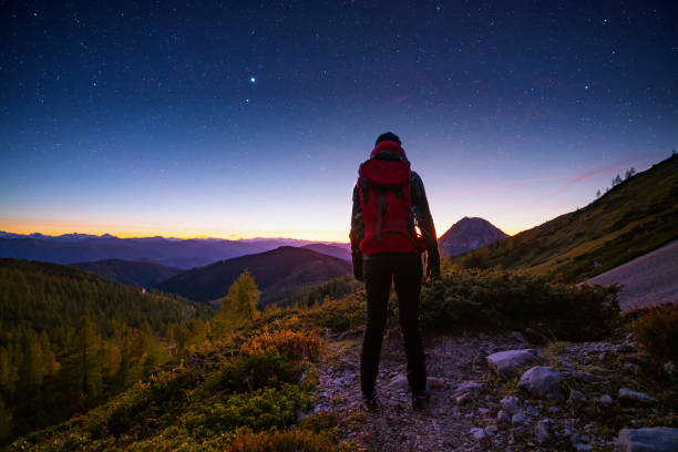 solo traveller high up in the mountains with starry heaven stock photo