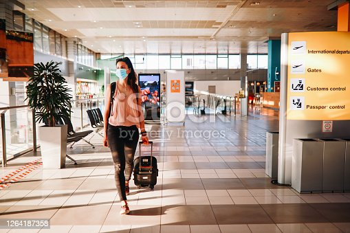 Young woman traveling solo in times of the coronavirus pandemic, looking at the info board, alone on the airport.