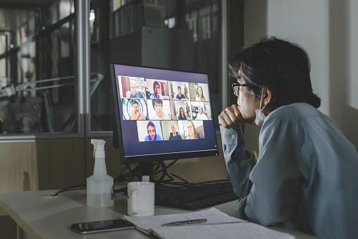 Solo worker attending to a group video conference meeting in the office, with remote team colleagues
