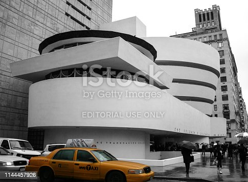New York, NY, USA - April 04, 2011: Solomon R. Guggenheim Museum with New York taxi highlighted in colour with remaining image in black and white. Image is taken from the street corner and has people walking with umbrellas.