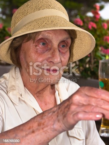 Portrait of very old lady with hat and glass of beer on Adriatic coast, Brac, Croatia.